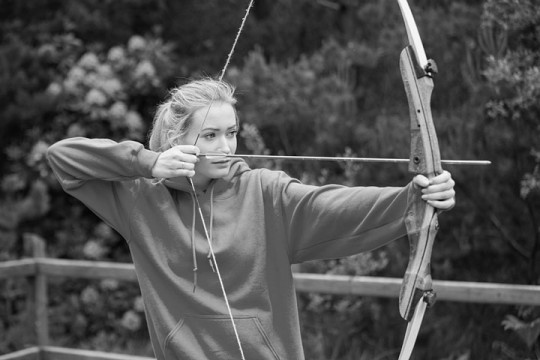 a young woman practicing at an archery range